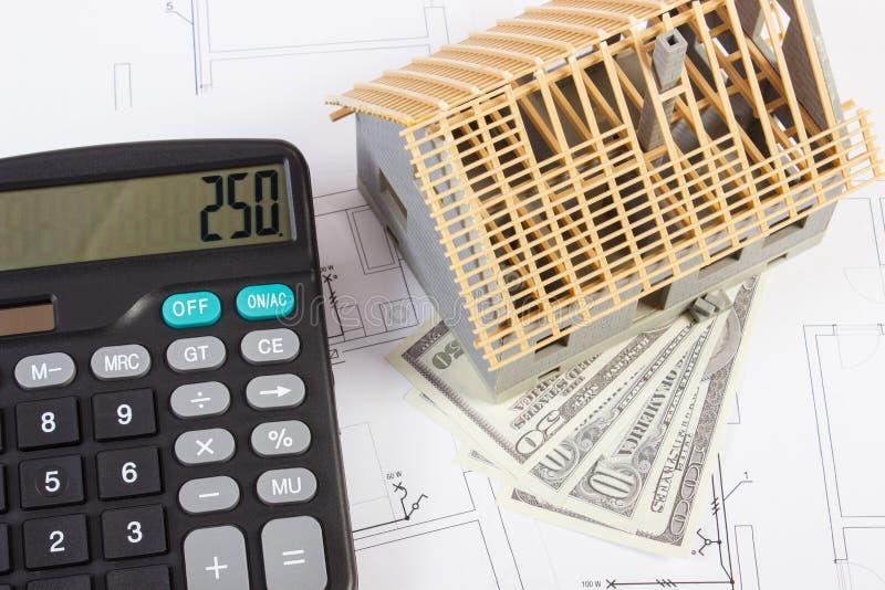 Casa bajo la construcción, la calculadora y dólar de las monedas en los dibujos y los diagramas eléctricos, concepto casero const fotografía de archivo libre de regalías