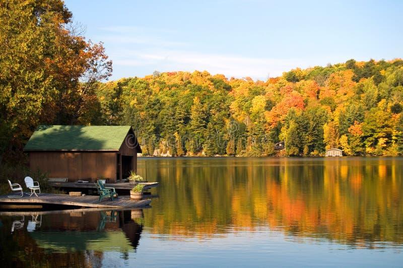 Casa barco y muelle en un lago hermoso con colores del otoño imágenes de archivo libres de regalías
