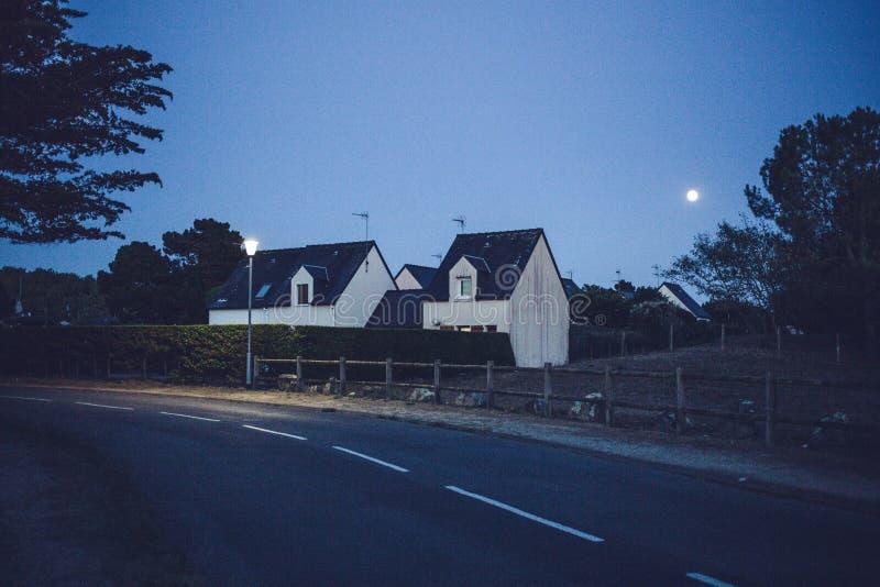 Casa bianca alla notte con la luce di luna al cielo notturno blu scuro immagini stock