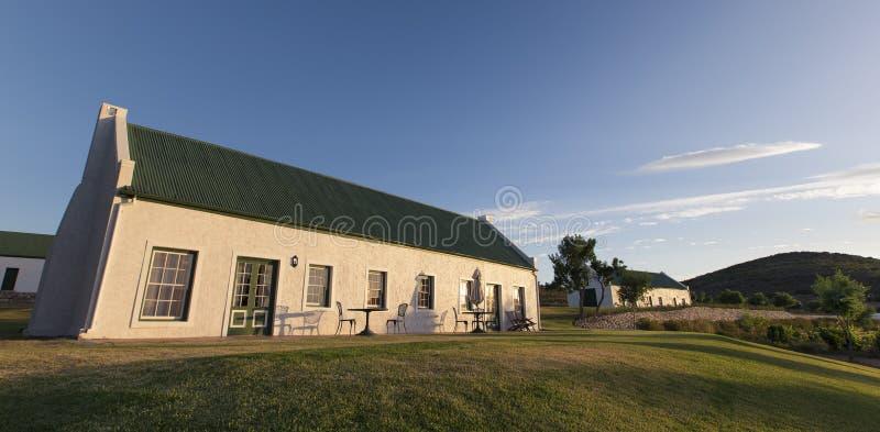 Casa bianca con il tetto verde al tramonto con un cielo blu immagini stock