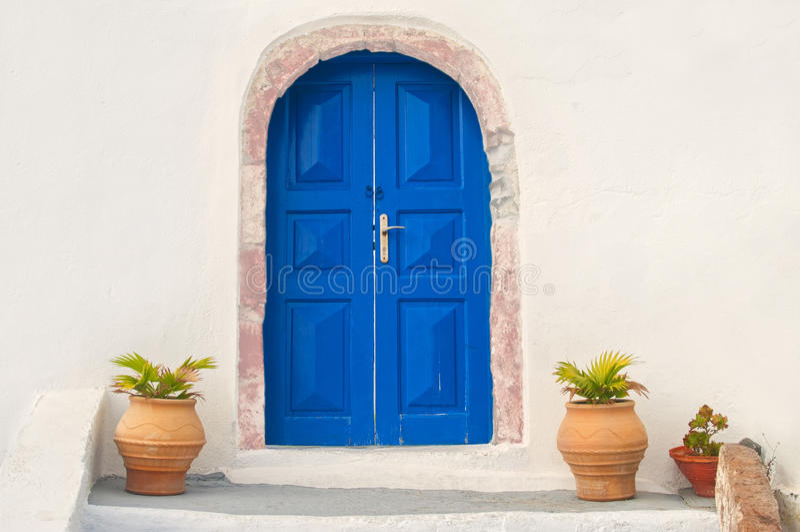 Casa bianca con la porta e le piante blu fotografia stock libera da diritti