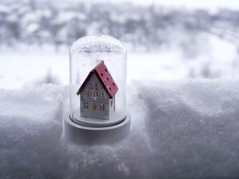 Casa bianca del giocattolo con un tetto rosso nella neve contro il contesto di un paesaggio di inverno immagini stock