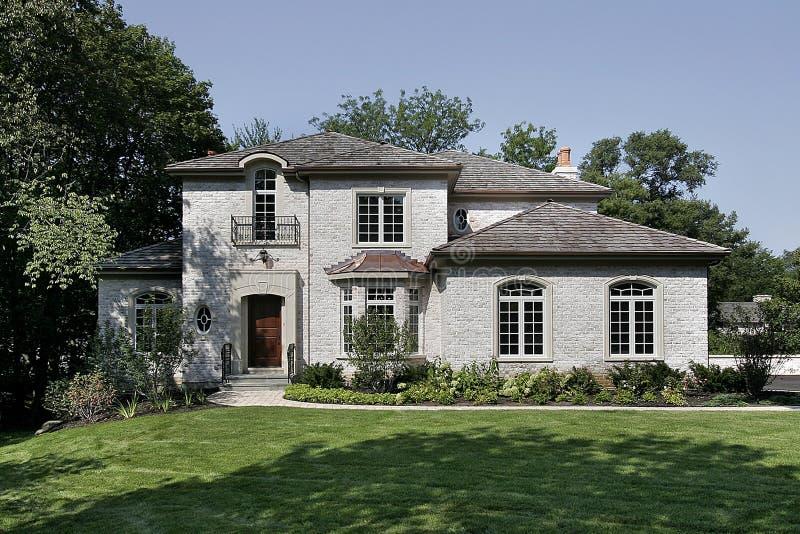 Casa bianca del mattone con il tetto di scossa del cedro fotografie stock libere da diritti