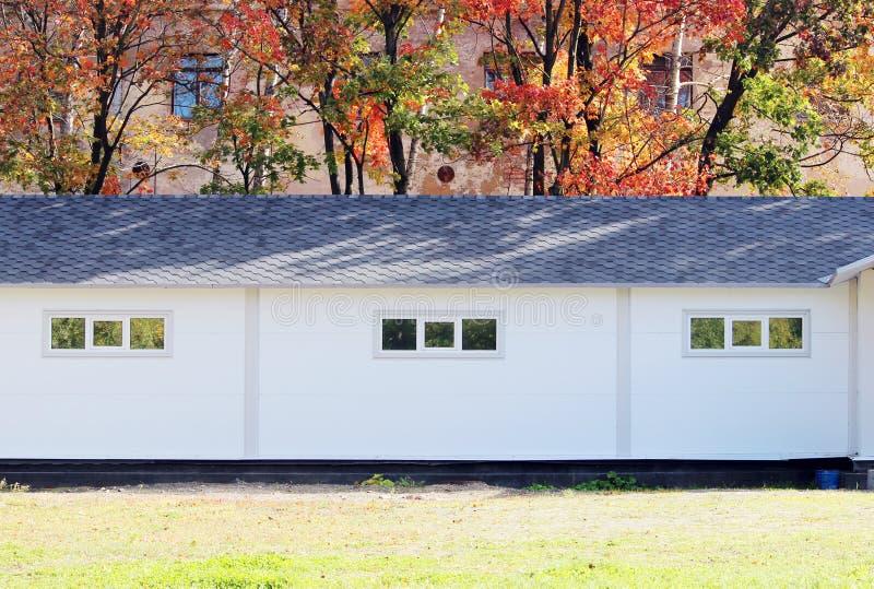 Casa bianca di struttura della parete, scatola scura, mattonelle marroni flessibili sui precedenti della foresta colorata multi d royalty illustrazione gratis