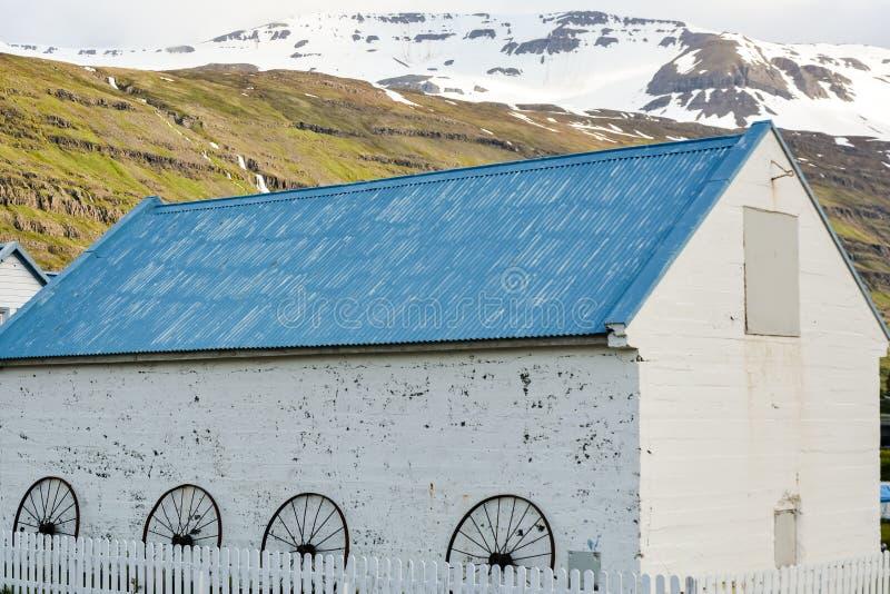 Casa blanca con el tejado azul en la pequeña ciudad Seydisfjordur en Islandia del este en verano con las montañas y la nieve fotografía de archivo