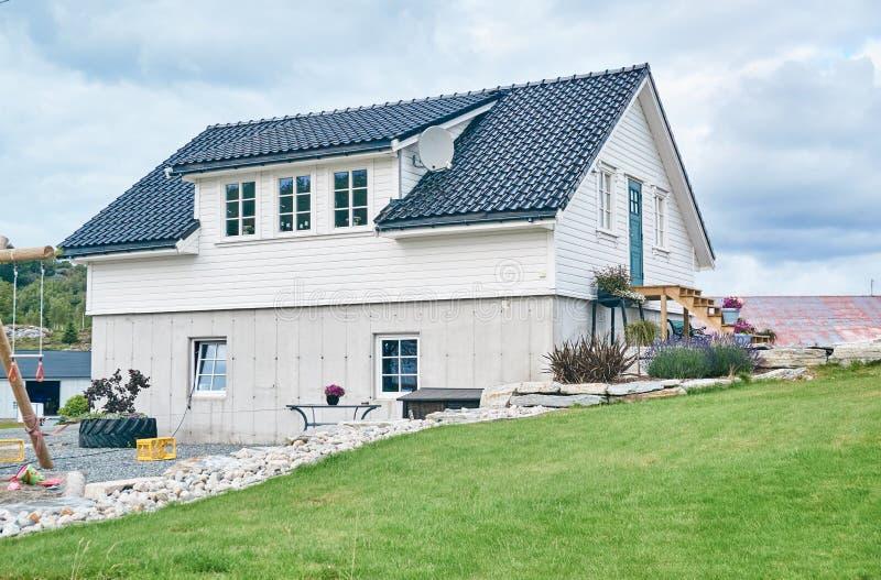 Casa blanca en el campo noruego, paisaje rural foto de archivo