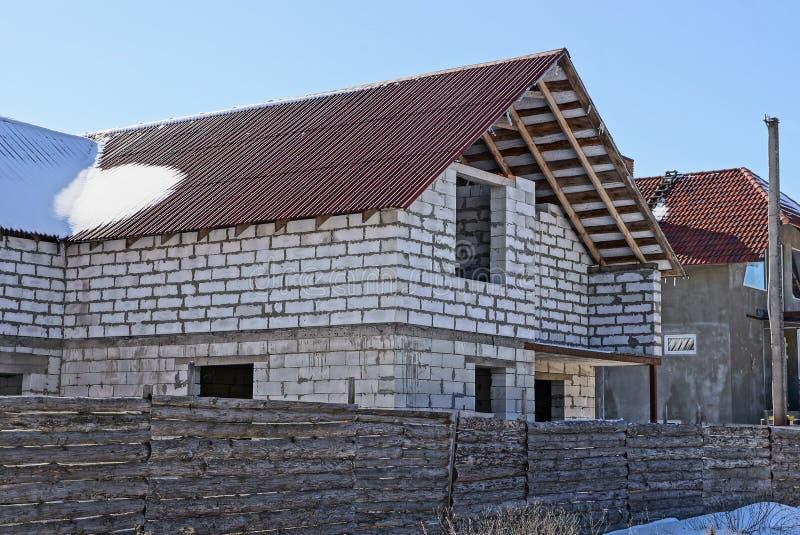 Casa blanca inacabada grande del ladrillo detrás de una cerca en la nieve imagenes de archivo