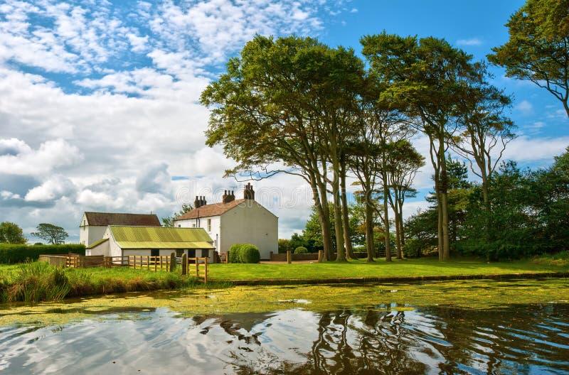 Casa blanqueada al lado de un canal imagenes de archivo