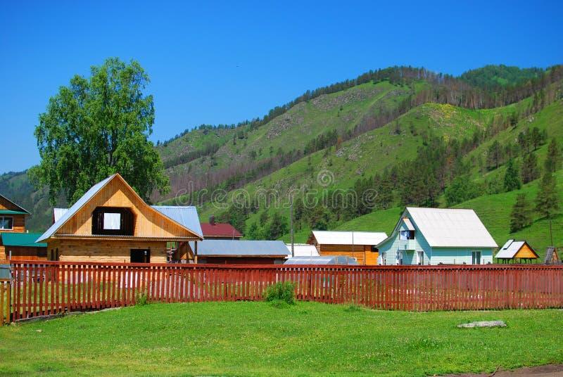 Casa bonita da vila com uma cerca nas montanhas foto de stock royalty free