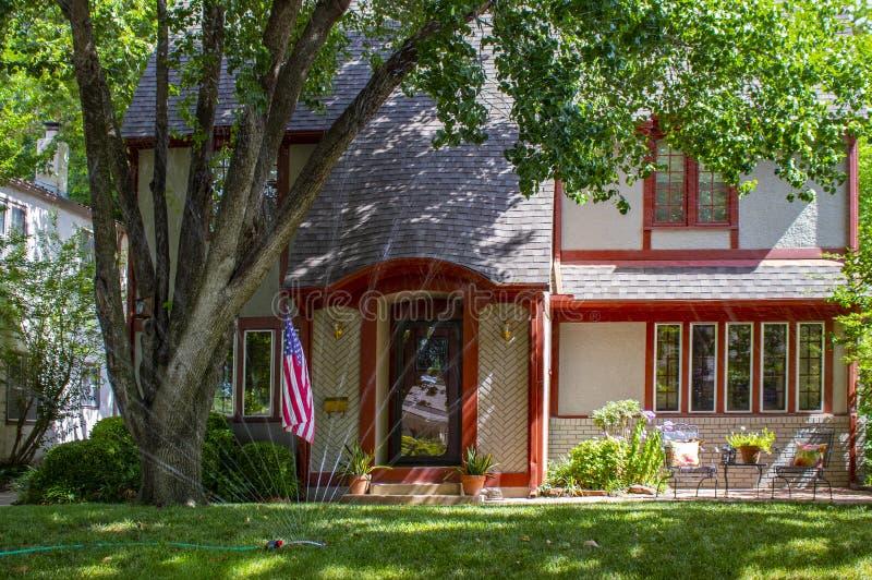 A casa bonita do tijolo aparou no vermelho com o pátio e as flores e as árvores grandes que indicam a bandeira americana com os s fotografia de stock