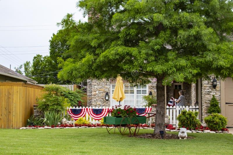 A casa bonito da rocha decorada para a 4o da estamenha de julho e as bandeiras com ajardinar agradável e uma árvore e uma mulher  imagens de stock