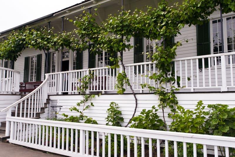 Casa branca com o sótão com uvas e bancos foto de stock