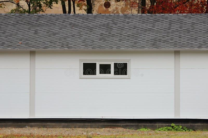 Casa branca da textura da parede, caixa escura, telhas marrons flexíveis no fundo da floresta multi-colorida do outono das folhas imagem de stock royalty free