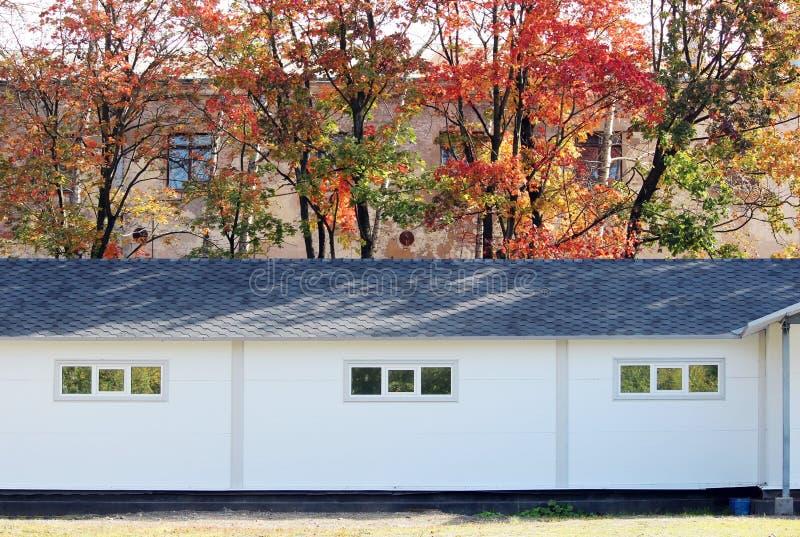 Casa branca da textura da parede, caixa escura, telhas marrons flexíveis no fundo da floresta multi-colorida do outono das folhas ilustração royalty free