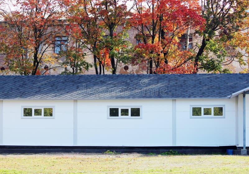 Casa branca da textura da parede, caixa escura, telhas marrons flexíveis no fundo da floresta multi-colorida do outono das folhas ilustração stock