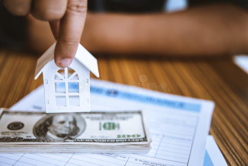 Casa branca do modelo da terra arrendada da mão na cédula do dólar Seguro e conceito dos bens imobiliários de investimento da pro foto de stock