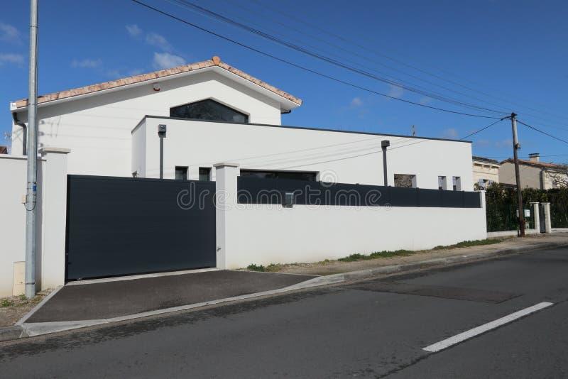 Casa branca e cinzenta recente com uma grande parede protetora e uma obscuridade - porta automática cinzenta fotos de stock royalty free