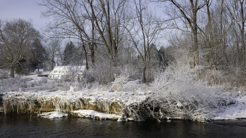 Casa branca na luz solar na distância com grama coberto de neve e no cacho no banco de rio na parte dianteira imagem de stock royalty free