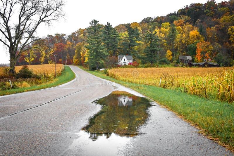 Casa branca refletida em uma poça da chuva na estrada na queda foto de stock
