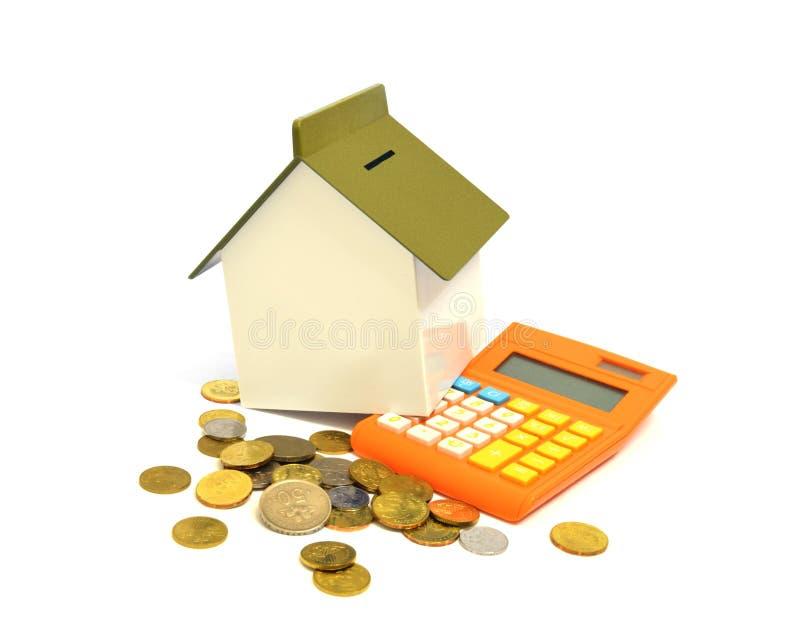 Casa, calculadora y monedas foto de archivo libre de regalías