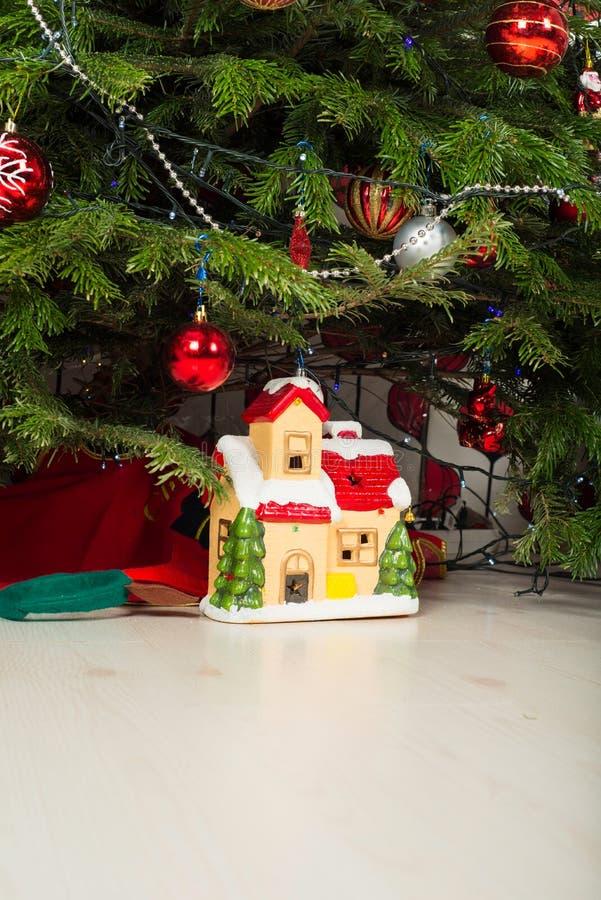 Casa cerâmica sob a árvore de Natal fotos de stock royalty free