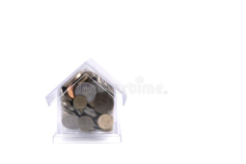 Casa-cerdo con un tubo Casa plástica transparente en un fondo blanco En las monedas del metal de la hucha de diferente fotos de archivo