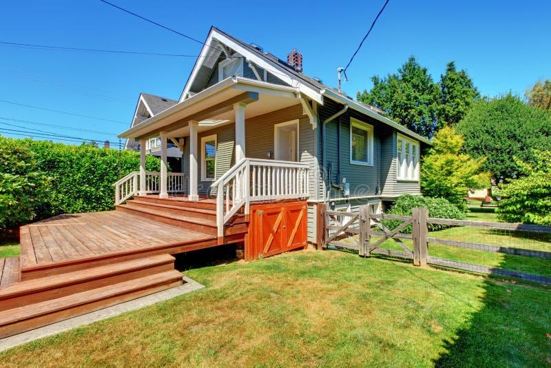 Casa cinzenta pequena com alpendre das traseiras e a cerca velha. fotografia de stock royalty free