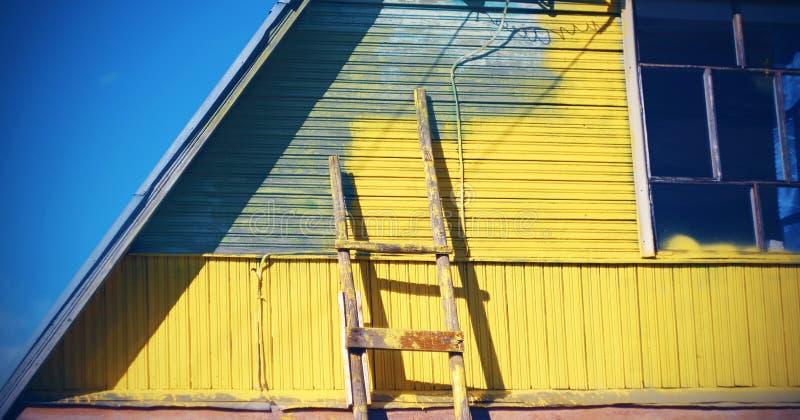 A casa cinzenta pintada no amarelo, perto da parede lá é uma escadaria, mas o processo do reparo é suspendido imagem de stock royalty free