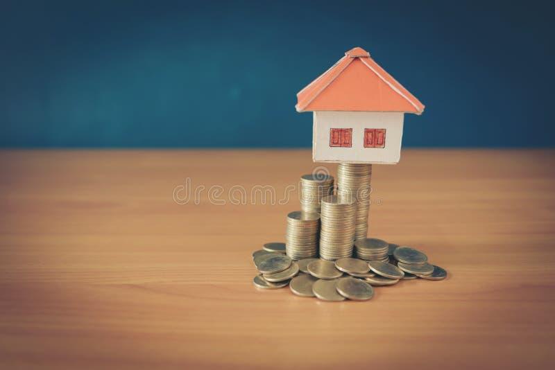 A casa colocada na mão dos homens das moedas está planejando o dinheiro das economias das moedas comprar um conceito para a escad imagens de stock