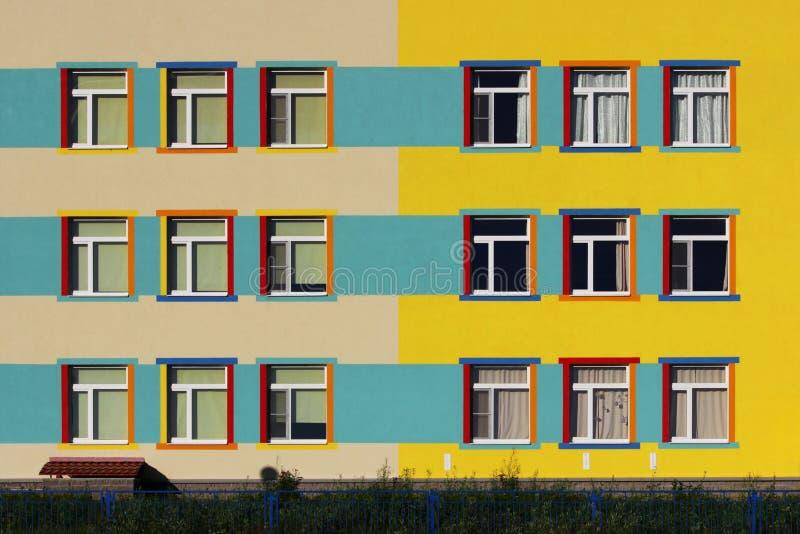 casa colorida agradable una guardería para los niños dieciocho colores de las ventanas, del azul, amarillos y beige fotos de archivo libres de regalías
