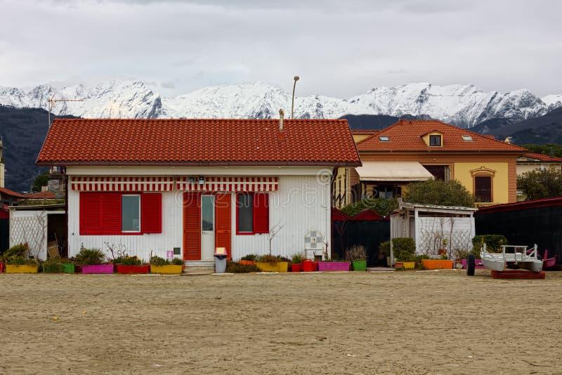 Casa colorida como salvavidas de la oficina en la playa de Versilia y de las montañas en fondo foto de archivo