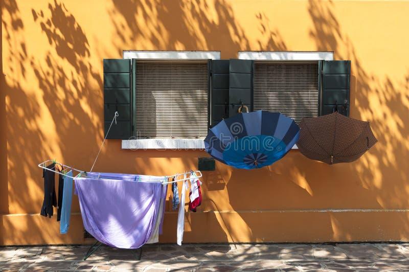 Casa colorida de la isla de Burano con el lavadero, Venecia, Italia imagenes de archivo