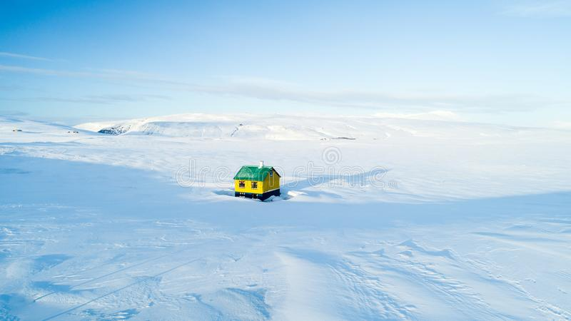Casa colorida só no meio do nada no céu azul da neve branca de Islândia do inverno foto de stock royalty free