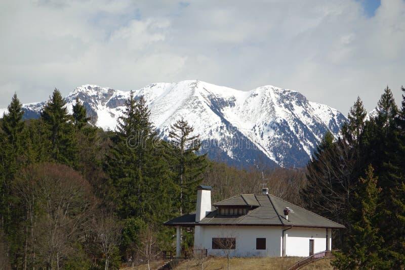 Casa com fundo tampado neve da montanha fotografia de stock royalty free