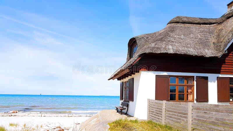 Casa com o telhado cobrido com sapê na costa imagens de stock