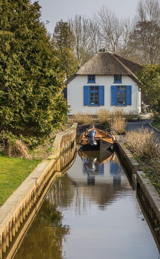 Casa com telhado cobrido com sapê e um barco em Giethoorn imagem de stock royalty free