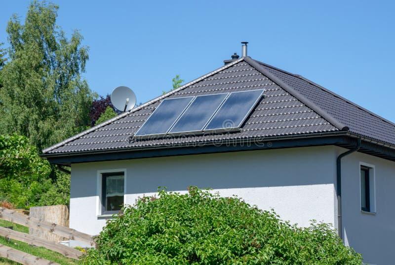 Casa com telhado telhado e o central elétrica térmico solar fotografia de stock royalty free