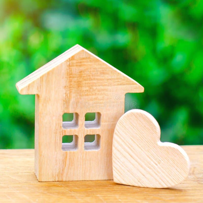Casa com um coração de madeira em um fundo verde Casa dos amantes foto de stock