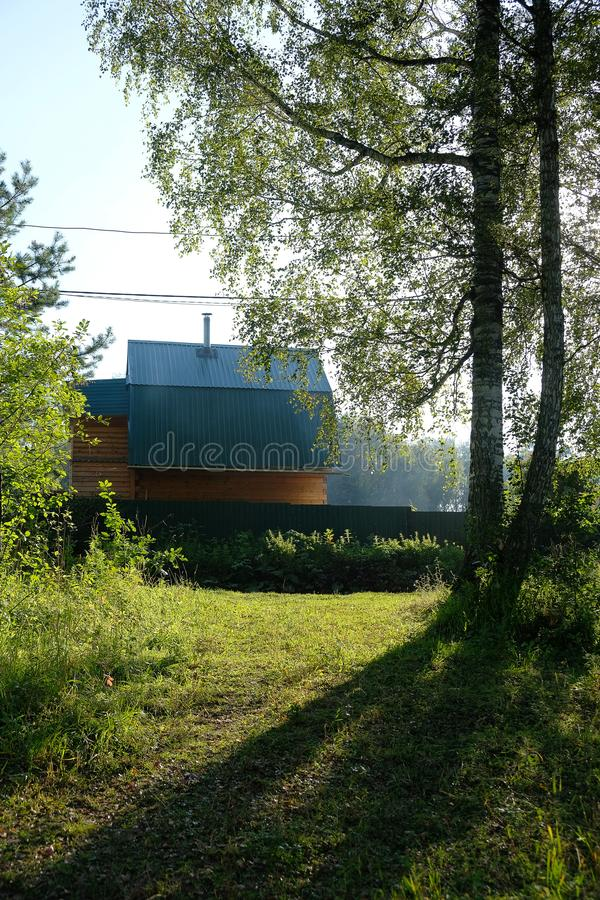 Casa com um telhado azul atrás de uma cerca, dois vidoeiros da vila no th foto de stock