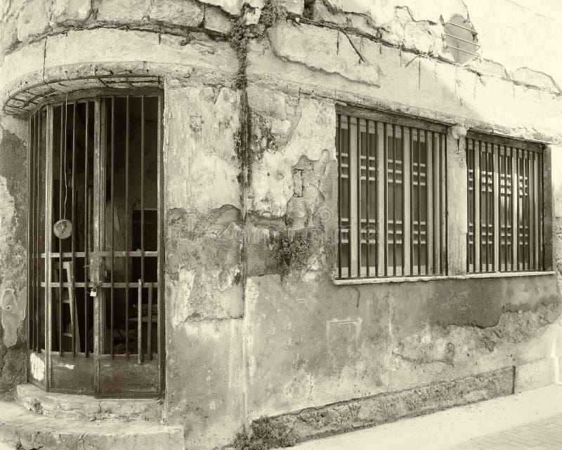 Casa comercial abandonada vieja de la sepia del vintage en una esquina con las paredes que desmenuzan y las barras de hierro que  fotos de archivo libres de regalías