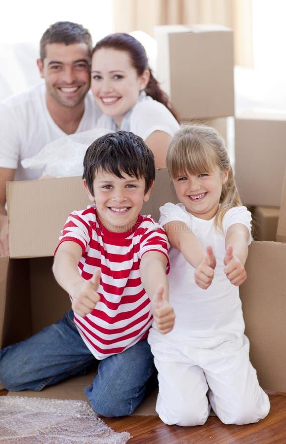 Casa commovente della famiglia con le caselle ed i pollici in su immagine stock libera da diritti