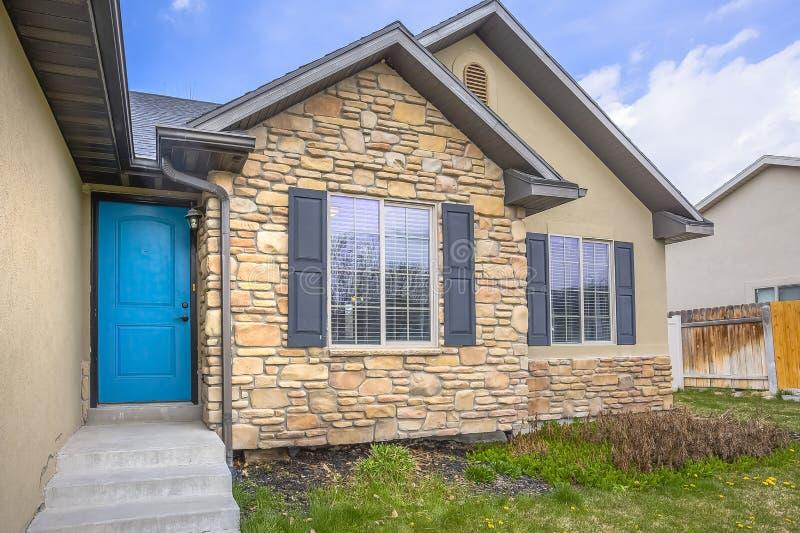 Casa con la parete di pietra e le finestre dell'entrata principale blu delle scale con gli otturatori di legno fotografia stock libera da diritti