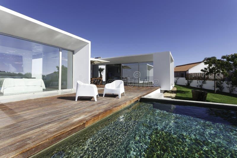Casa con la piscina del jardín y la cubierta de madera fotografía de archivo libre de regalías