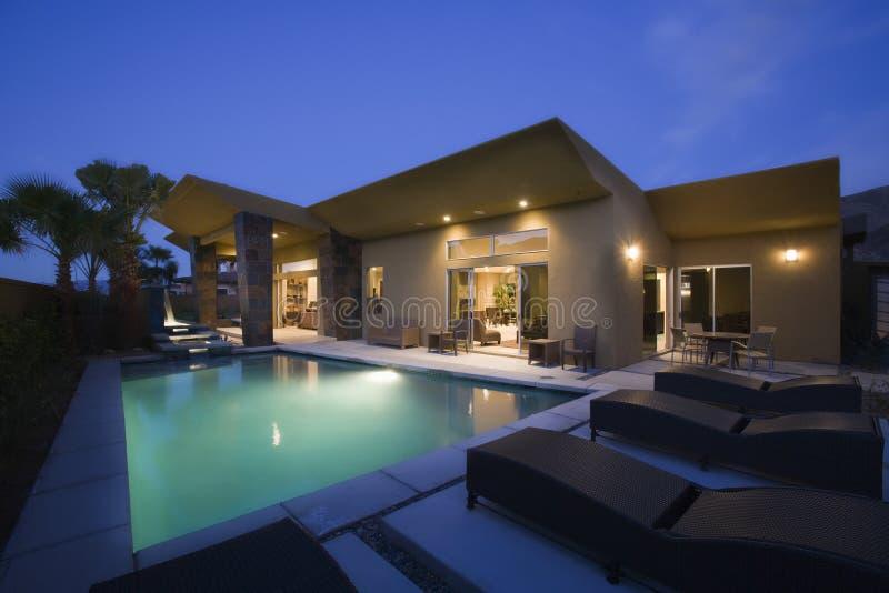 Casa con la piscina en la noche fotos de archivo