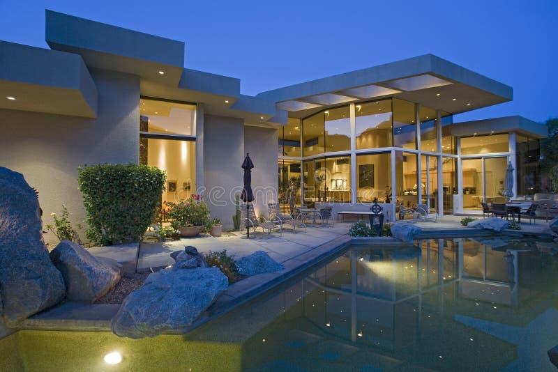 Casa con la piscina en patio trasero en la oscuridad foto de archivo