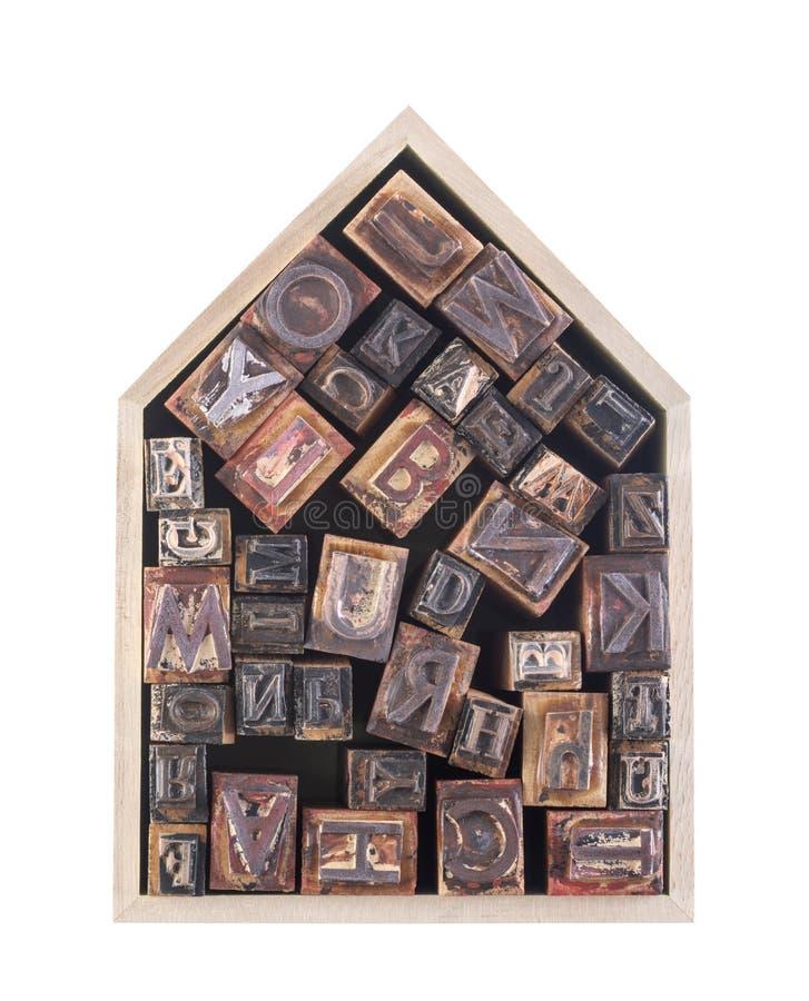 Casa con las letras de molde de madera aisladas en el fondo blanco imagen de archivo