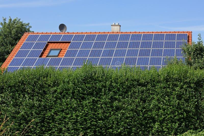 Casa con los moduls solares con un seto imagen de archivo libre de regalías