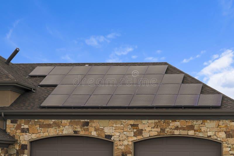 Casa con los paneles solares en el tejado contra el cielo azul con las nubes foto de archivo libre de regalías