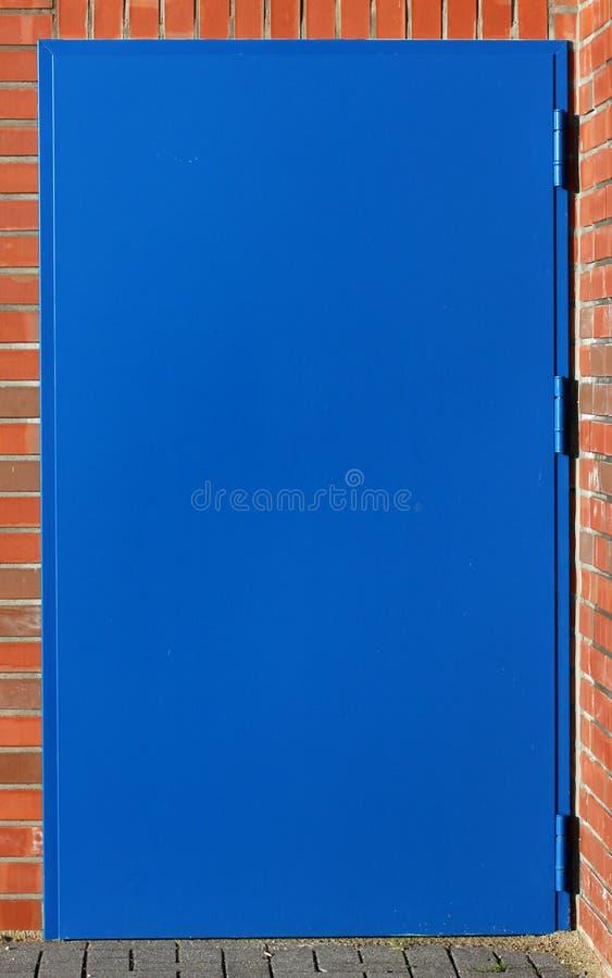 Casa con mattoni a vista della porta dei blu acciai fotografia stock