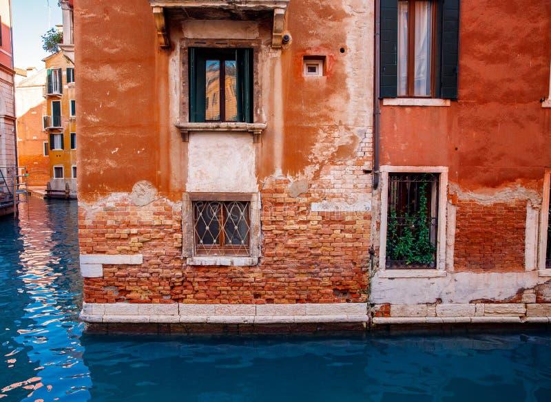 Casa con mattoni a vista rossa in città sul canale blu Venezia, passaggi stretti dell'acqua fra le costruzioni immagine stock